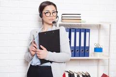 企业女孩秘书在一个白色办公通话中心坐 图库摄影