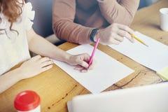 企业学生会议在办公室,妇女人特写镜头递在纸板料,布局的空的空间的文字 固定式在木头 免版税库存图片