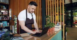 企业家与在输入和写笔记本的花店的膝上型计算机一起使用 影视素材