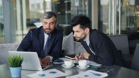 企业家争论在见面在咖啡馆期间谈论图使用膝上型计算机 股票录像