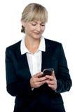 企业家在她的移动电话的读取消息 免版税库存图片