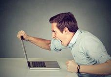 企业家恼怒和愤怒与一台膝上型计算机在他的办公室 库存图片