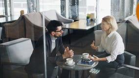 企业家成熟男人和妇女谈的开会在咖啡馆的桌上一起 股票录像