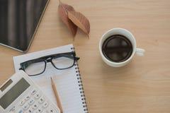 企业对象在办公室 杯子咖啡和片剂在木桌上 库存照片