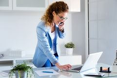 企业少妇谈话在手机,当使用她的膝上型计算机在办公室时 免版税库存照片