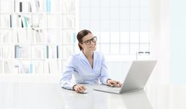 企业微笑的妇女或工作在她的办公桌机智的干事 库存照片
