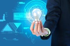 企业想法。拿着电灯泡的商人。 库存照片