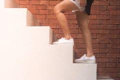 企业成功概念:妇女走白色具体台阶外面在大厦有橙色砖背景 免版税库存照片