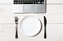 企业或饮食概念、工作场所有膝上型计算机的和空的板材有利器的 免版税库存照片