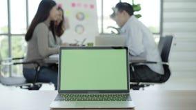 企业技术概念-数字式生活方式运作的办公室 有绿色屏幕的便携式计算机在桌上在办公室 特写镜头