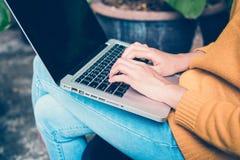 企业技术概念-运作在办公室外的数字式生活方式 妇女递有黑屏的键入的便携式计算机 库存图片