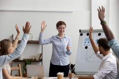 企业教练员带领的不同的公司成员举手 库存照片