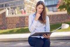 读企业文件的可爱的妇女在公园 免版税库存图片