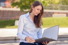 读企业文件的可爱的妇女在公园 免版税库存照片