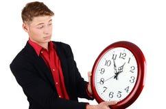 企业时间。举行和看对一个大时钟的商人。 免版税库存照片