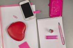企业有桃红色笔的,唇膏,构成袋子,电话工作书桌 免版税库存照片