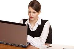 企业服务台膝上型计算机坐妇女工作 库存图片