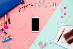 企业框架flatlay与妇女` s蓝色袋子、玻璃、智能手机有黑copyspace的,化妆用品和固定式供应 免版税图库摄影