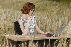 企业概念坐在书桌使用在领域的一台计算机的射击了一个美丽的少妇 免版税库存照片