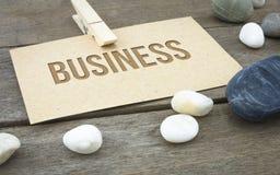 企业概念性词有与包装纸板料或笔记的木背景 库存图片