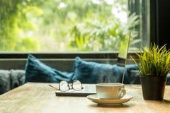 企业概念有膝上型计算机和镜片的咖啡杯在木桌上 免版税库存照片