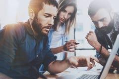 企业概念查出的小组白色 谈论年轻的专家新的事务在现代办公室射出 小组三个人分析 免版税库存图片