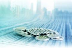 企业概念,在新闻纸的硬币堆与都市风景 库存图片