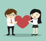 企业概念,爱在办公室 商人和女商人拿着红色心脏并且感到愉快 免版税库存照片