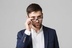 企业概念-一个英俊的商人的画象在衣服的与玻璃严肃认为与紧张表情 Isol 库存图片