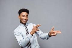 企业概念-与指向其他的手指的快乐的愉快的年轻非裔美国人的举行的枪标志 免版税库存照片