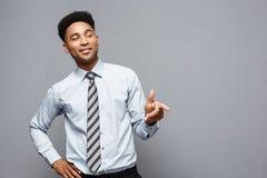 企业概念-与指向其他的手指的快乐的愉快的年轻非裔美国人的举行的枪标志 免版税图库摄影