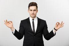 企业概念-做凝思和瑜伽的英俊的白种人商人画象在工作前 免版税库存图片