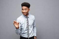 企业概念-显示在他前面的确信的快乐的年轻非裔美国人好手指与惊奇 库存图片