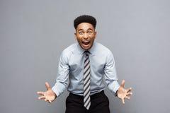 企业概念-显示在他前面的确信的快乐的年轻非裔美国人手与失望的表示 免版税库存图片