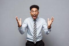 企业概念-显示在他前面的确信的快乐的年轻非裔美国人手与失望的表示 库存图片