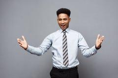 企业概念-显示在他前面的确信的快乐的年轻非裔美国人手与惊奇的表示 免版税库存照片