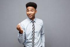 企业概念-显示在他前面的确信的快乐的年轻非裔美国人手与惊奇的表示 库存图片