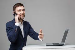 企业概念-显示赞许和微笑的确信的面孔在他的膝上型计算机前面的画象英俊的商人 库存图片
