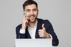 企业概念-显示重击和在他的膝上型计算机前面的画象英俊的商人微笑的确信的面孔 白色backgr 免版税库存图片