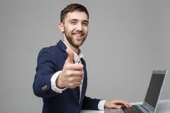 企业概念-显示重击和在他的膝上型计算机前面的画象英俊的商人微笑的确信的面孔 免版税图库摄影