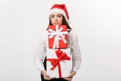 企业概念-有拿着有忧虑脸面护理的圣诞老人帽子的美丽的年轻白种人女商人很多礼物盒 免版税库存照片