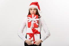 企业概念-有拿着有忧虑脸面护理的圣诞老人帽子的美丽的年轻白种人女商人很多礼物盒 免版税库存图片