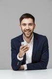 企业概念-演奏moblie电话和微笑与膝上型计算机的衣服的画象英俊的愉快的英俊的商人对工作offi 图库摄影