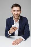 企业概念-演奏moblie电话和微笑与膝上型计算机的衣服的画象英俊的愉快的英俊的商人对工作offi 库存照片