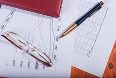 企业概念玻璃、笔记本和笔 库存照片
