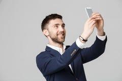 企业概念-画象英俊的商人采取selfie他自己与智能手机 奶油被装载的饼干 图库摄影