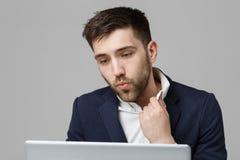 企业概念-看在膝上型计算机的衣服震动的画象英俊的紧张商人工作 奶油被装载的饼干 免版税库存图片