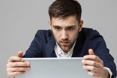 企业概念-看在膝上型计算机的衣服震动的画象英俊的紧张商人工作 奶油被装载的饼干 免版税图库摄影