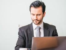企业概念-看在膝上型计算机的衣服震动的画象英俊的紧张商人工作 免版税库存图片