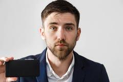 企业概念-英俊的商人采取selfie他自己与智能手机 奶油被装载的饼干 图库摄影
